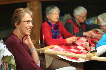 Thérèse Broglie, à gauche, Rosmarie Waelti, Irma Ruefenacht, et Helena Wiedmer confectionnent un quilt qui sera offert à l'œuvre d'entraide du MCC.
